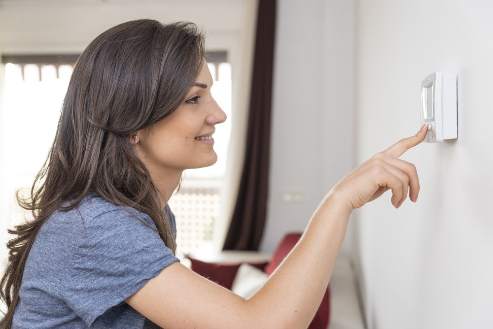 woman setting a thermostat for her air conditiong